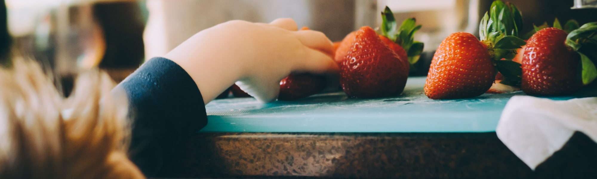 Hand reaching out for strawberries